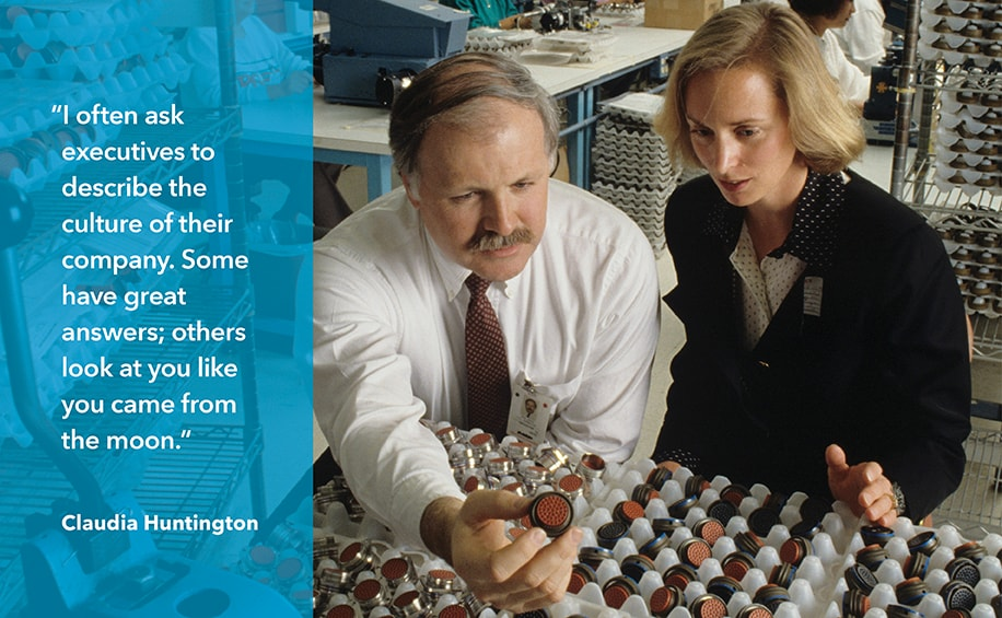 "Photo depicts Claudia Huntington speaking with a company representative on a research visit to Matrix Science Corporation in Torrance, California, circa 1990. Pull-quote at left reads: ""I often ask executives to describe the culture of their company. Some have great answers; others look at you like you came from the moon."" Claudia Huntington."