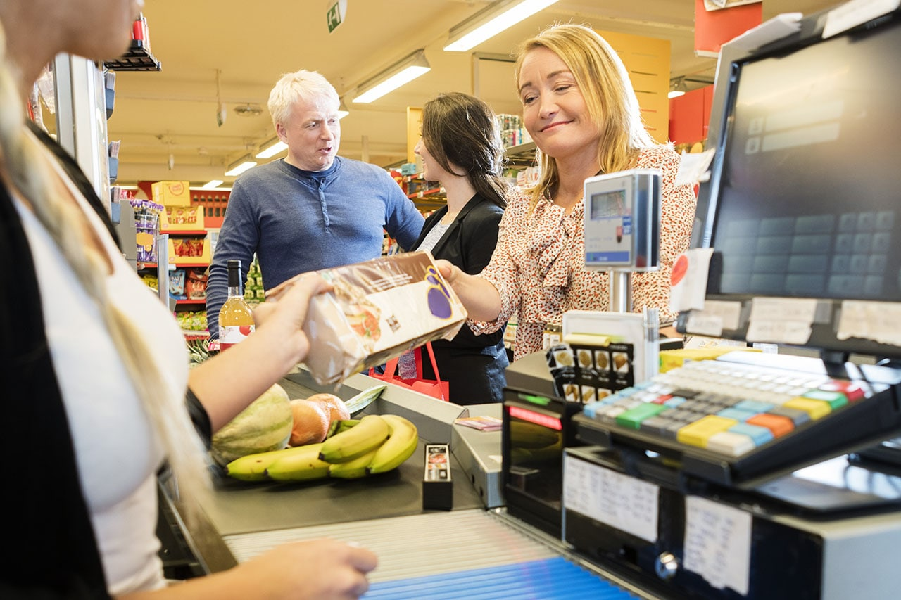 Smiling customer giving packet to female cashier at checkout counter in supermarket