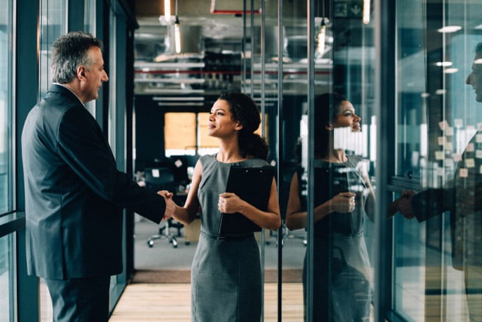 Woman and man shaking hands in an office