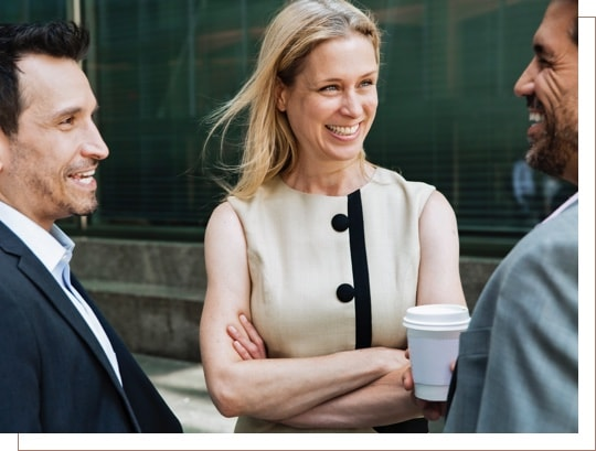 A woman and two men laughing while talking over coffee in a business setting.