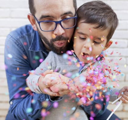Father and son playing with confettis