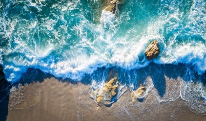 Aerial view of waves crashing into rocks and onto the shore